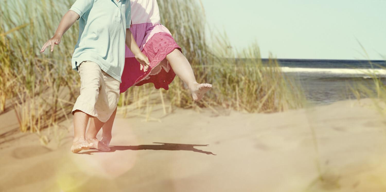Enfants jouant sur la plage derrière une dune