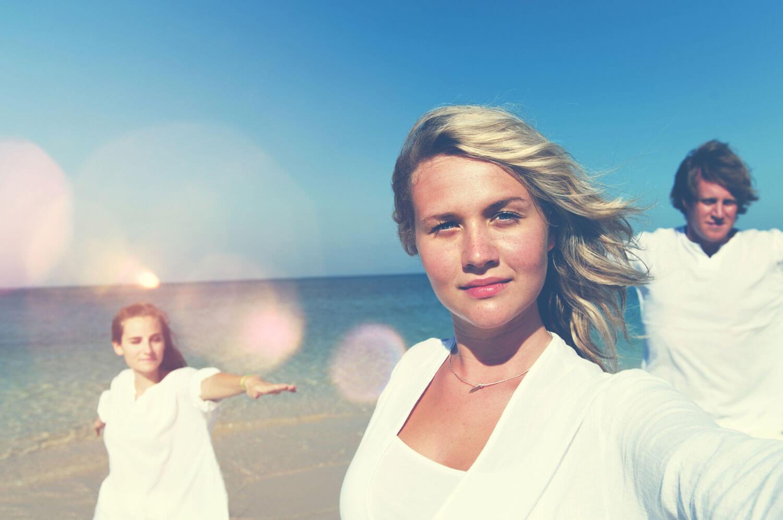 Famille habillée en blanc sur la plage profitant d'une légère brise et du soleil
